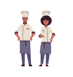 Cooks couple professional chefs standing together vector