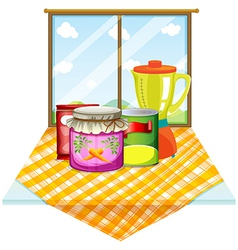 A table near the window with foods inside vector