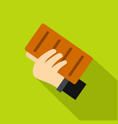 Hand holding a brick icon flat style vector