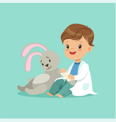 Cute baby boy heals paw of toy bunny little vector