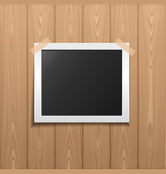 Photo frame placed on a wooden background vector