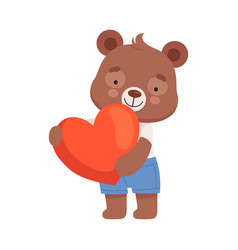 Smiling bear character holding red heart in his vector