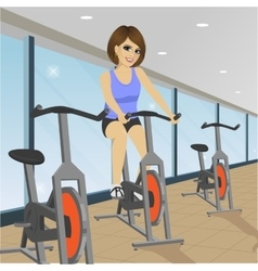 young woman doing indoor biking exercise at gym vector image vector image