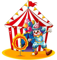 A clown holding balloons near the ring of fire vector image