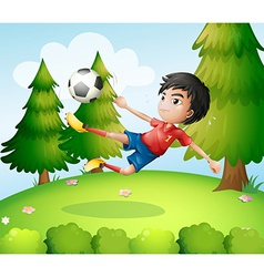 A boy playing soccer near the pine trees vector image vector image