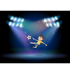 A boy kicking the soccer ball at the stage vector