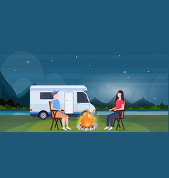 couple sitting around campfire at night near vector image