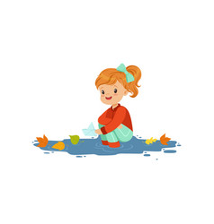Sweet redhead little girl in warm clothing playing vector