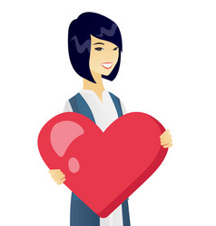 young asian business woman holding a big heart vector image