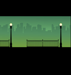 Silhouette of street lamp with city background vector