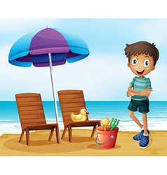A young boy at the beach near the wooden chairs vector