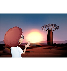 A curly boy watching the sunset in the desert vector image vector image