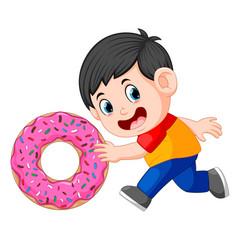 A boy pushing big donut vector