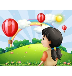 A girl looking at the hot air balloon vector