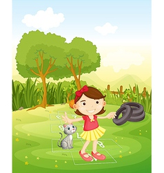 A girl playing at the park with her cat vector image