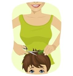 Little boy getting a haircut at barber shop vector