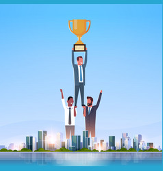 Successful businessmen group holding golden cup vector