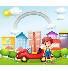 A boy and his red car near the high buildings vector