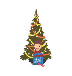 Cute boy sitting next to christmas tree with gift vector