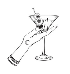 Martini with eyeballs cocktail in hand of witch vector