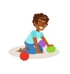 little boy sitting and playing with colorful balls vector image