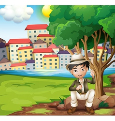 A man sitting above the rock under the tree vector