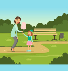 mother giving cotton candy to her daughter while vector image