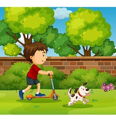 Boy riding on scooter in the yard vector image
