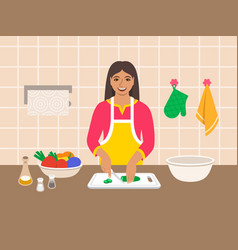Indian woman cuts vegetables for salad in kitchen vector