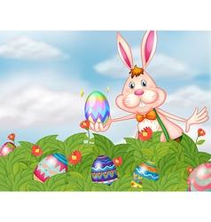 A bunny with eggs at the garden vector image