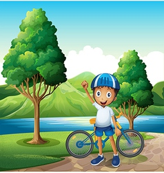 A smiling young boy at the riverbank with his bike vector