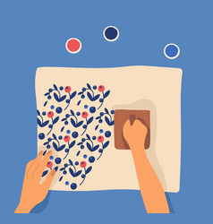 Hands printing pattern on fabric using woodblocks vector