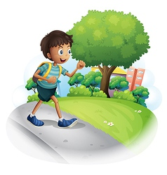 A boy with a bag walking along the street vector image