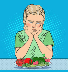 Pop art unhappy boy with plate of fresh vegetables vector