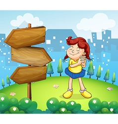 A little girl standing beside the wooden arrow vector image