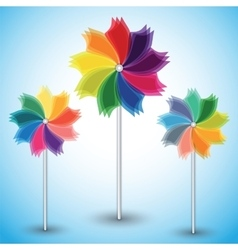 Three colorful windmills on blue background vector
