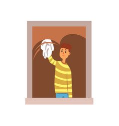 Smiling teenager boy washing window with rag vector