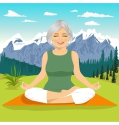 Senior woman meditating in mountains vector