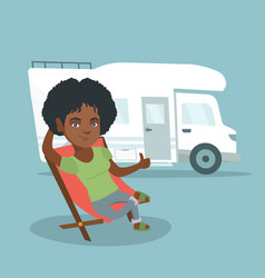 Woman sitting in a chair in front of camper van vector