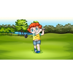 A young boy playing golf at the field vector image