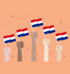 Hands holding up netherlands flags vector