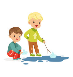 Cute little boys playing with paper boats in a vector