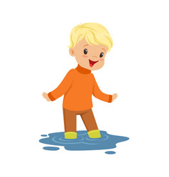 Cute blonde little boy playing on a puddle wearing vector