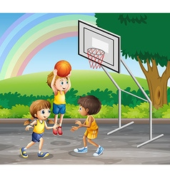 Three children playing basketball at the court vector