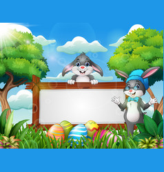 two cute rabbits near the blank sign and easter eg vector image