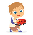 young boy playing his red toy car vector image