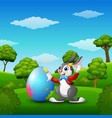 cartoon easter bunny painting easter eggs in the p vector image