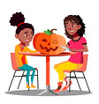 mother and daughter making a pumpkin for halloween vector image