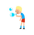 cute blonde little boy blowing soap bubbles vector image vector image
