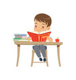 cute boy sitting at the desk and reading a book vector image vector image